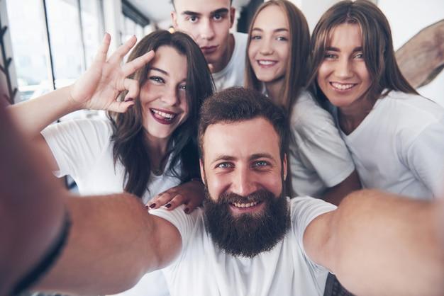 Um grupo de pessoas faz uma foto de selfie em um café. os melhores amigos reunidos em uma mesa de jantar comendo pizza e cantando várias bebidas