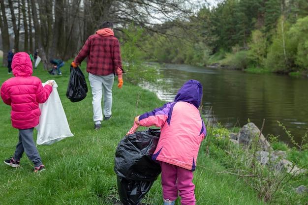 Um grupo de pessoas limpa o lixo na saída da floresta, na primavera