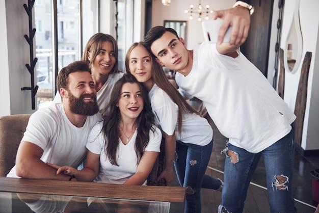 Um grupo de pessoas tira uma foto de selfie em um café. os melhores amigos reunidos em uma mesa de jantar