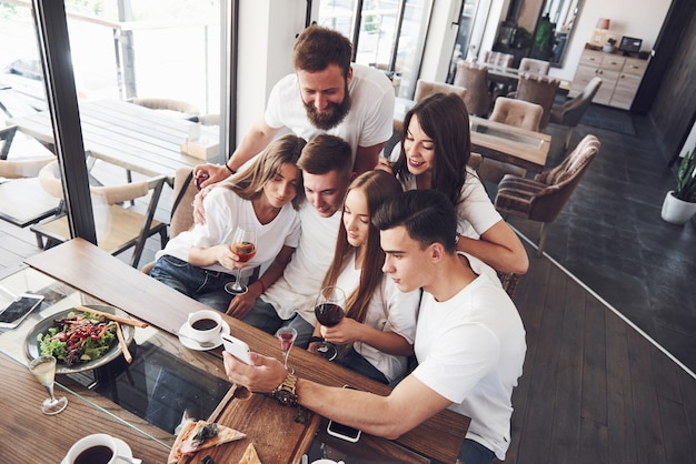 Um grupo de pessoas tira uma foto de selfie em um café. os melhores amigos se reuniram em uma mesa de jantar comendo pizza e cantando vários drinks.