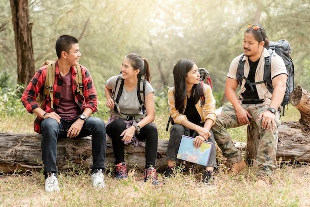 Um grupo de quatro turistas asiáticos está discutindo, discutindo, planejando na floresta.