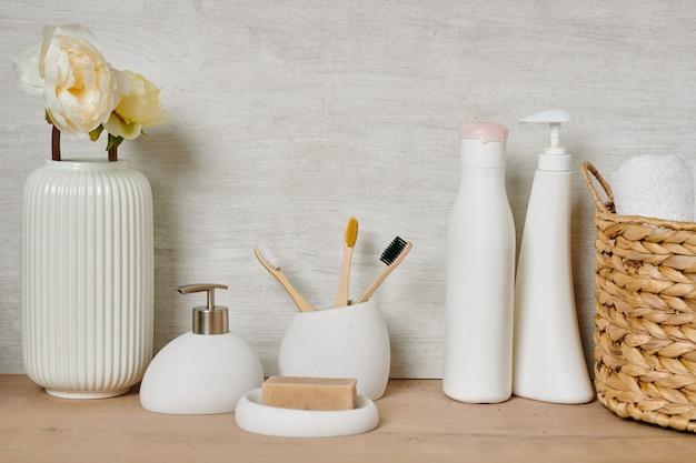 Um grupo de recipientes brancos com material de cuidado corporal, cesta com toalhas limpas e vaso com flores