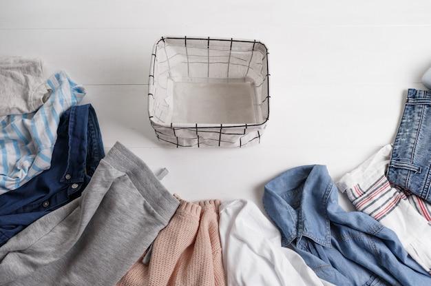 Um grupo de roupas de algodão orgânico colocado em uma mesa branca está pronto para ser dobrado em cestas brancas