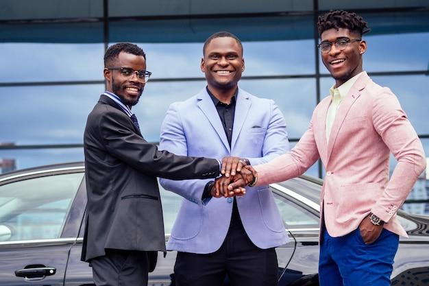 Um grupo de três elegantes amigos empresário afro-americano, empresários da moda, ternos de negócios, reunião com o aperto de mão em um verão ao ar livre. conceito de bom negócio de sucesso