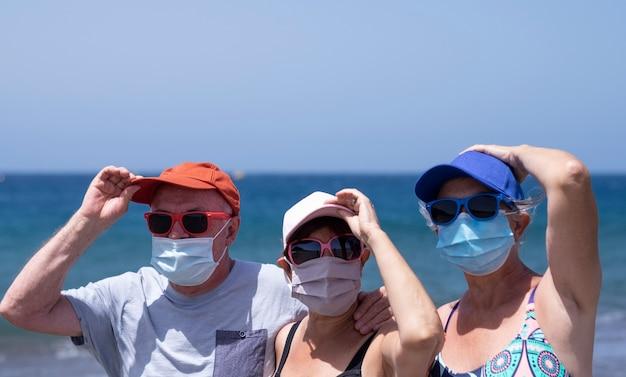 Um grupo de três idosos curtindo as férias na praia, segurando chapéus