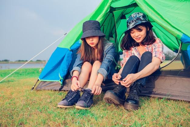 Um grupo de turistas asiáticos amigos amarre um sapato perto da barraca com felicidade no verão enquanto acampava