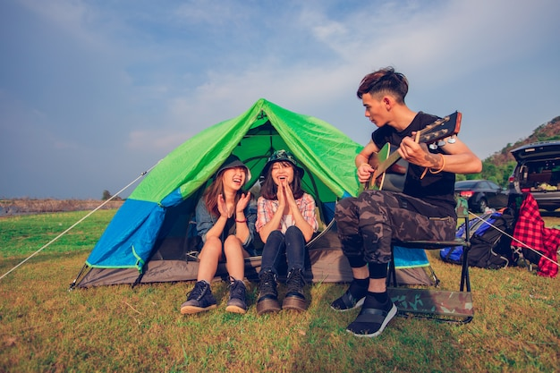 Um grupo de turistas asiáticos amigos bebendo e tocando violão, juntamente com a felicidade no verão enquanto acampar perto do lago ao pôr do sol