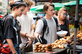 Um grupo de turistas que compram comida tailandesa na barraca de comida