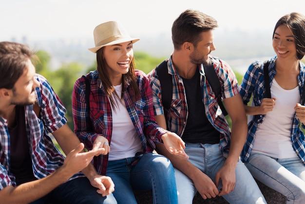 Um grupo de turistas sentado em um banco no parque e falando.