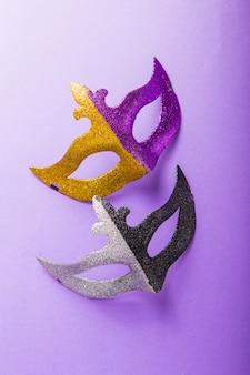 Um grupo festivo, colorido de carnaval ou máscara carnivale em um fundo roxo. máscaras venezianas.
