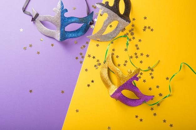 Um grupo festivo, colorido de carnaval ou máscara de carnivale em um fundo roxo amarelo. máscaras venezianas.