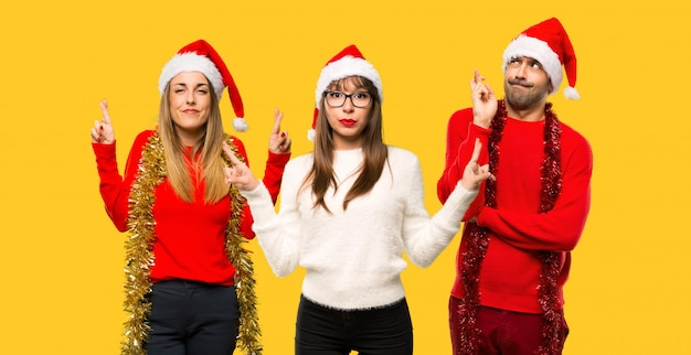 Um, grupo pessoas, loiro, mulher, vestido, para, natal, feriados, com, dedos cruzando