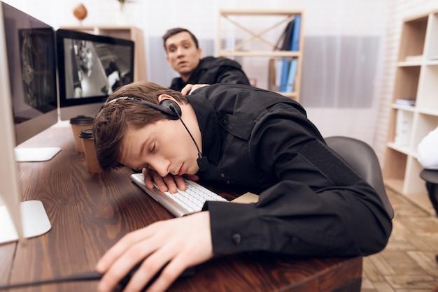 Um guarda de homem está dormindo no local de trabalho.