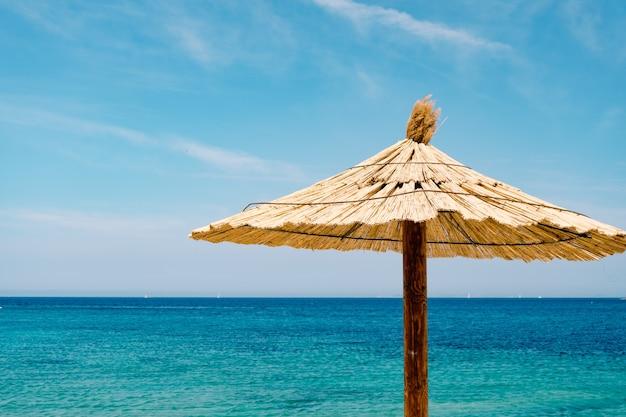 Um guarda-sol de palha contra o céu azul e água azul em uma praia arenosa