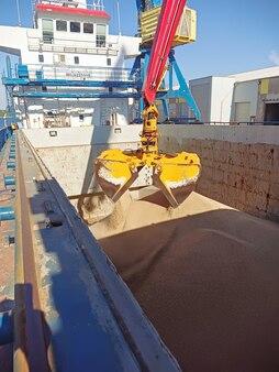 Um guindaste com uma caçamba de manipulador carrega trigo em um navio de carga seca no porto de carga agrícola