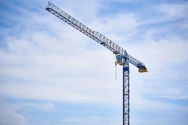 Um guindaste de alta altitude contra um céu azul nublado.