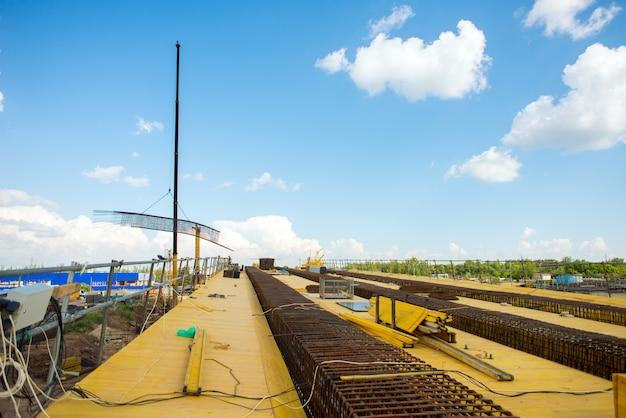 Um guindaste de construção levanta uma gaiola de reforço durante a construção de uma ponte de transporte