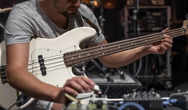 Um guitarrista montando efeitos de processamento de áudio de guitarra no palco.