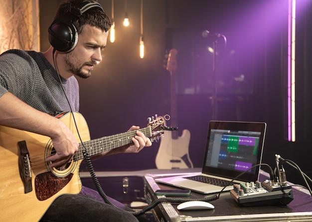 Um guitarrista toca violão com fones de ouvido conectados a um mixer de som. forma de onda digital no monitor do laptop.