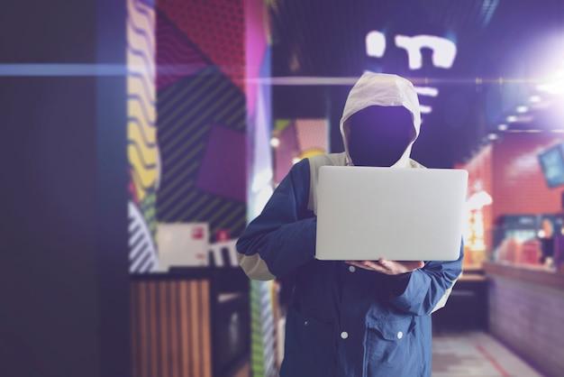 Um hacker anônimo no capô com computador, quebra de informações digitais