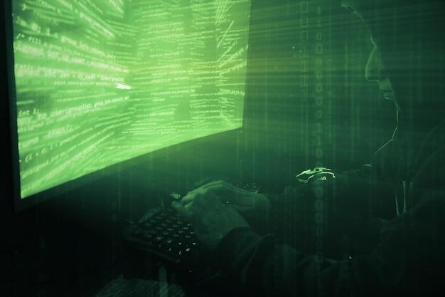 Um hacker de capuz em um quarto escuro