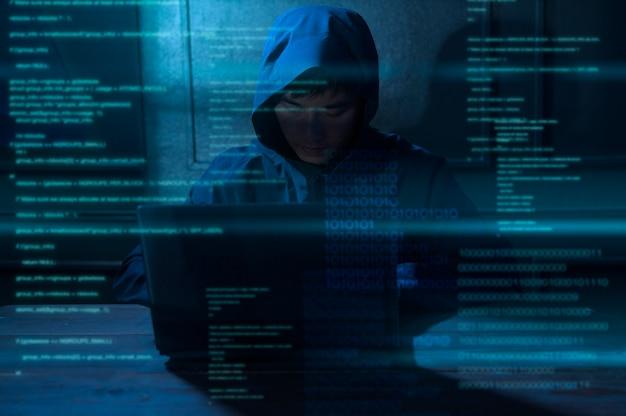 Um hacker está usando um laptop para roubar dados durante a noite