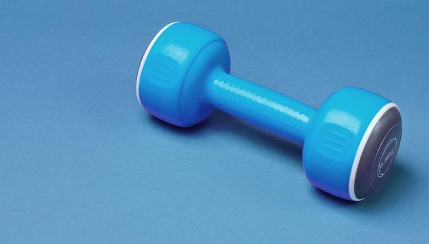 Um haltere de plástico azul sobre fundo azul.
