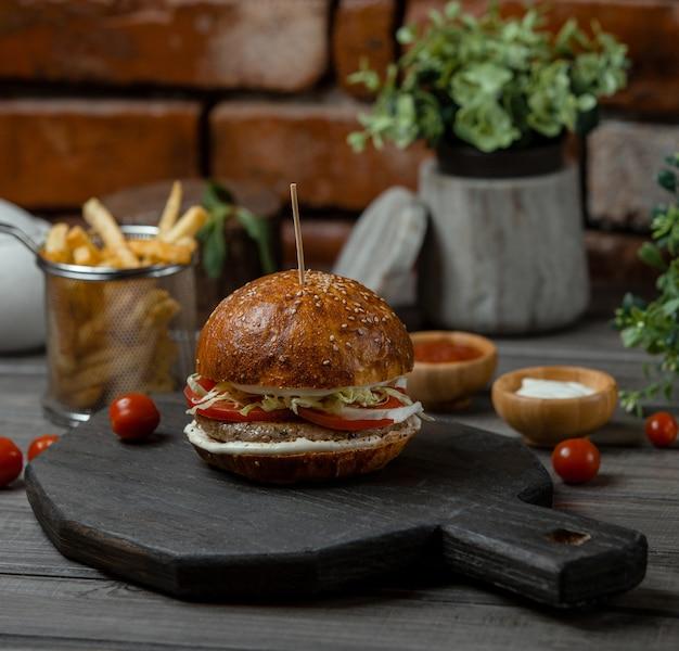 Um hambúrguer de carne recheado com legumes e aperitivos e servido com batatas fritas.