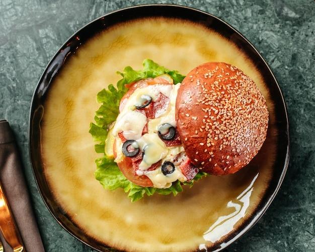 Um hambúrguer de vista superior com queijo azeitonas e legumes diferentes dentro da panela redonda no chão brilhante