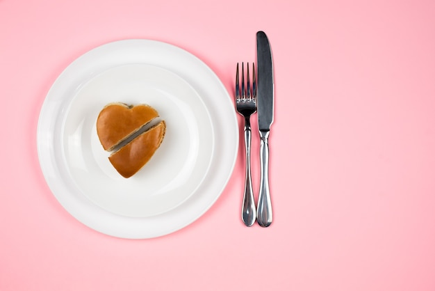 Um hambúrguer em forma de coração aberto num prato branco. a vista do topo. conceito de dia dos namorados.