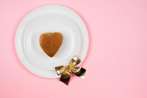 Um hambúrguer em forma de coração num prato branco. a vista do topo. conceito de dia dos namorados.