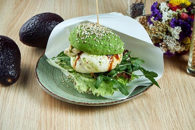 Um hambúrguer incomum feito com metades de abacate, como pãezinhos com queijo burrata e rúcula. visão. comida saudável e verde. vegano