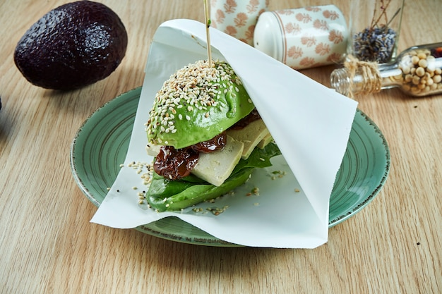Um hambúrguer incomum feito com metades de abacate, como pãezinhos com queijo tofu e tomates secos ao sol. visão. comida saudável e verde. vegano