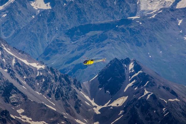 Um helicóptero amarelo em um fundo de montanhas