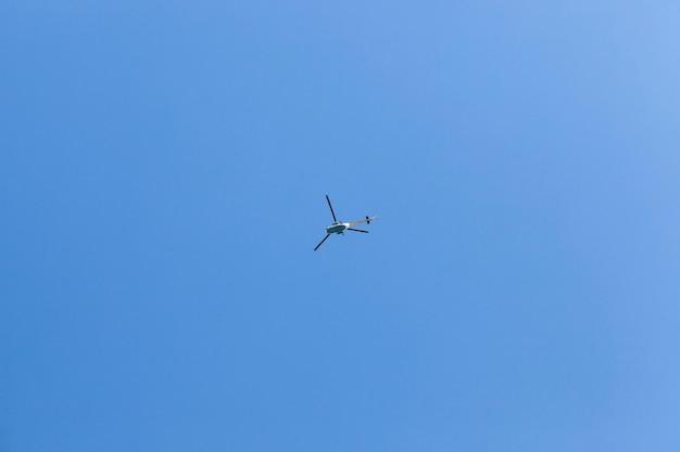 Um helicóptero voando lentamente em um céu azul, uma vista inferior