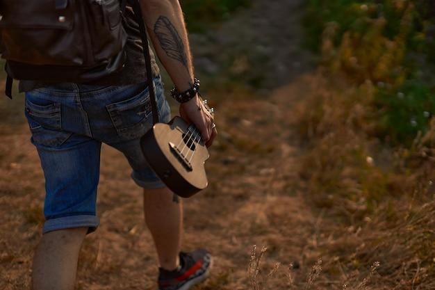 Um hippie de short jeans e com uma tatuagem no braço caminhando perto da floresta segurando um ukulele ...