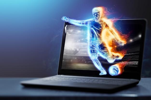 Um holograma de um jogador de futebol correndo para fora de um notebook, tela de laptop. o conceito de apostas esportivas, futebol, jogos de azar, transmissão online de futebol.