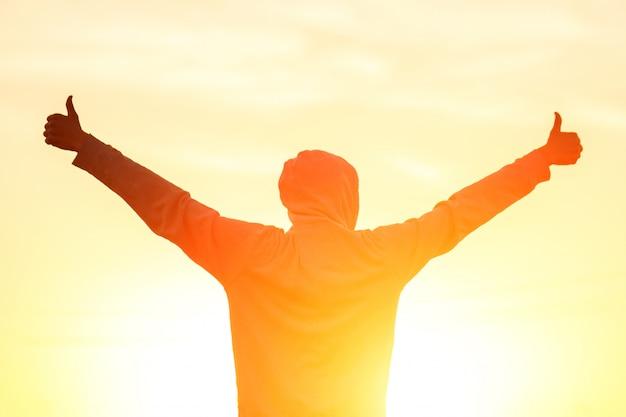 Um homem à luz do pôr do sol com as mãos para cima