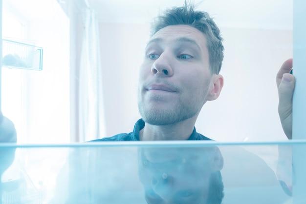 Um homem abre a geladeira para pegar algo para comer, vista de dentro