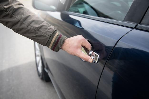 Um homem abre a porta de um carro
