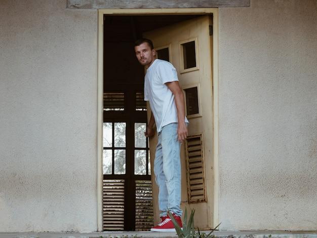 Um homem abre a porta de uma casa abandonada.