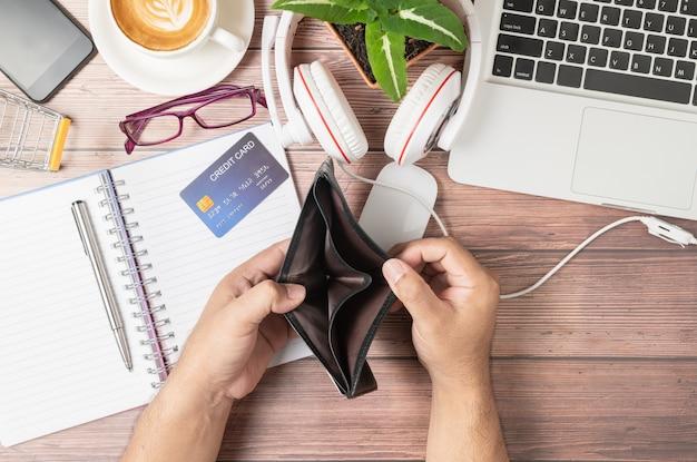 Um homem abre carteira sem dinheiro na mesa que consiste em cartões de crédito no notebook