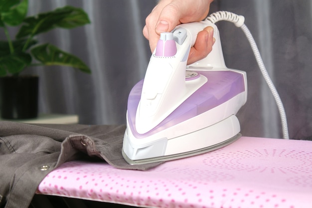 Um homem acaricia um lençol com um ferro elétrico em uma tábua de passar