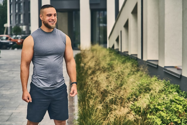 Um homem adulto alegre e musculoso em uma camiseta cinza e shorts azul escuro saiu para treinar