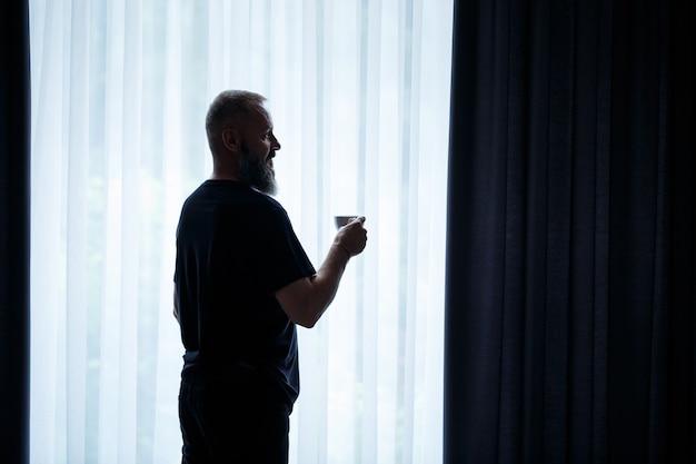 Um homem adulto com barba bebe café e olha pela janela. conceito de recreação de campo de dia útil
