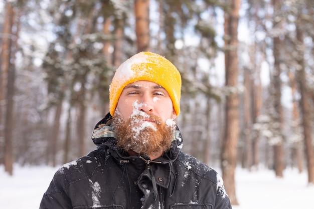 Um homem adulto com barba em uma floresta de inverno todo o rosto na neve, congelado, infeliz com o frio