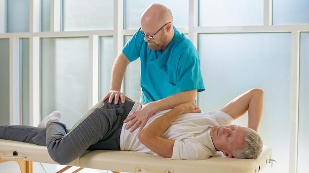 Um homem adulto treina força muscular com um médico profissional em uma clínica de reabilitação moderna phy ...