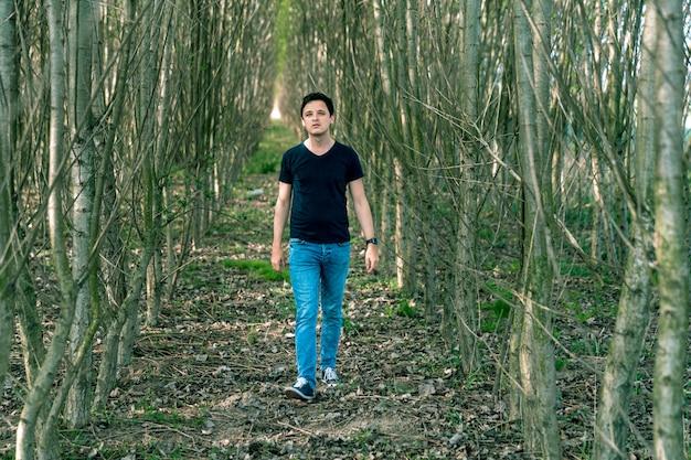 Um homem afinado positivamente em uma caminhada na floresta experimenta uma sensação de sucesso
