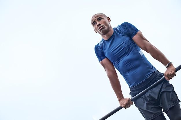 Um homem africano está se levantando em uma academia ao ar livre