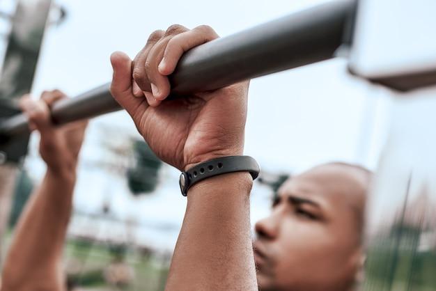Um homem africano se exercitando em uma academia ao ar livre